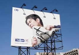 man tearing billboard